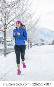 Attractive Woman jogging outdoors during winter weather and snow on the ground. Vertical photo of a woman working out during the winter months