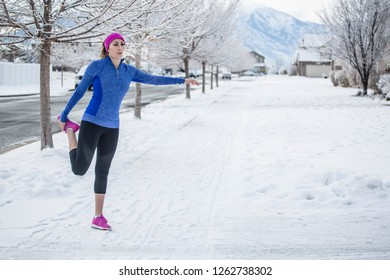 Attractive Woman jogging and stretching outdoors during winter weather and snow on the ground. Horizontal photo of a woman working out during the winter months