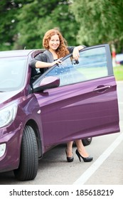 Attractive woman with keys standing near own car