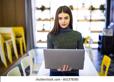 attractive woman with laptop smiling in modern office