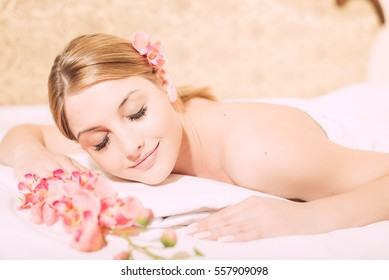 Attractive woman laying on massage spa bed white background, Closeup portrait