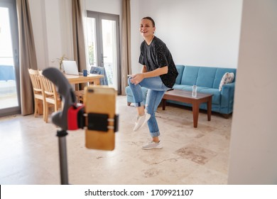An attractive woman learns to dance online in the living room in her apartment. Stay home concept, entertainment and online education