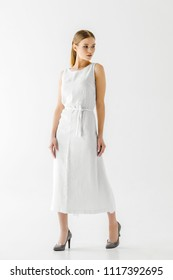 attractive woman in linen white dress looking away isolated on grey background