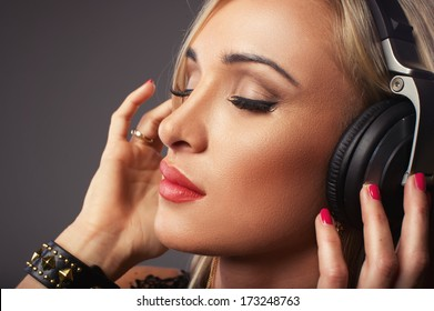 Attractive woman listening music through headphones, eyes closed.