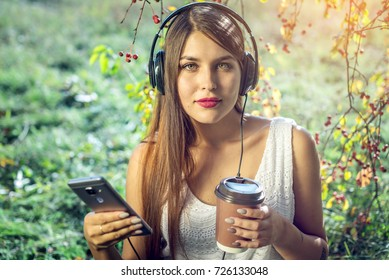 Attractive woman listening to music in your phone wearing headphones and holding a Cup of coffee in hand on a Sunny day in the Park. The concept of audiobooks and student education