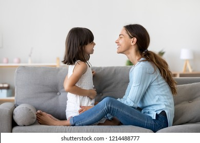 Attractive woman and little girl sitting on comfortable couch at home. Young mother talking communicates with small adorable daughter. Best friends happy motherhood weekend together with kid concept