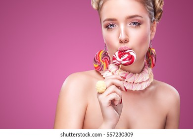 Attractive woman with lollipop in hand on pink background