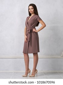 Attractive woman with long brunette hair dressed in fashionable brown wrap around midi dress with short sleeves smiling and posing. Laughing female model standing against white wall on background.