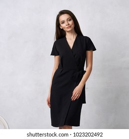 Attractive woman with long brunette hair dressed in fashionable black wrap around midi dress with short sleeves smiling and posing. Laughing female model standing against white wall on background.