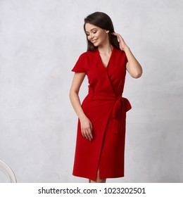 Attractive woman with long brunette hair dressed in fashionable red wrap around midi dress with short sleeves smiling and posing. Laughing female model standing against white wall on background.