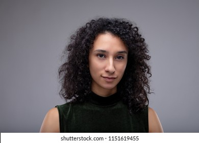 Attractive woman with long curly dark hair looking pensively at the camera isolated on grey