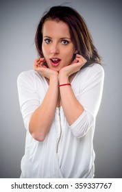 Attractive woman with a look of amazement, astonishment or shocked surprise holding her hands to her cheeks with her mouth open, upper body over grey