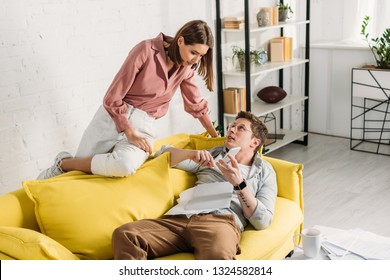 attractive woman looking at boyfriend with smartphone lying on sofa