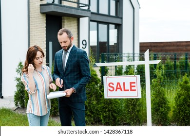attractive woman looking at clipboard while standing near broker and house