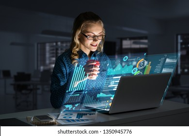 Attractive woman looking at her laptop screen sitting in night office. Mixed media