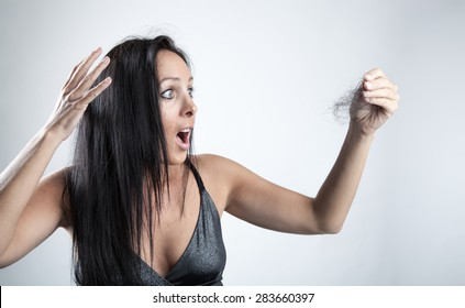 Attractive woman is looking shocked to her lost hair