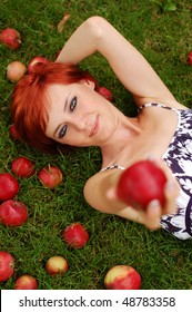 Attractive woman lying on the grass and offering an apple.