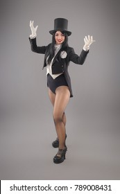 Attractive woman magician dressed in costume suit doing magic imagination performance. Studio shoot
