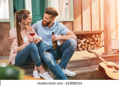 attractive woman and man resting with beer and wine on porch