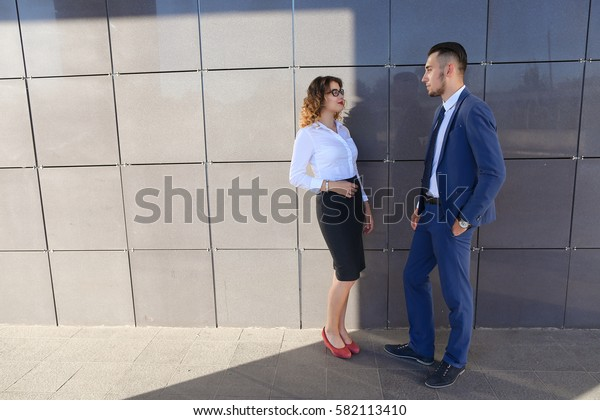 Attractive woman and man, young entrepreneurs, students and friends discuss important issues, share business ideas, smiling, laughing, make decisions, solve problems and stand next to each other near