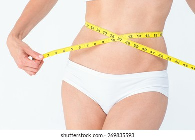Attractive woman measuring her belly on white background