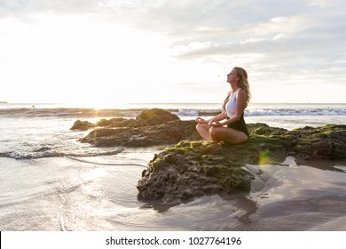 attractive woman meditating finding her inner peace on a beautiful afternoon at the beach in Costa Rica