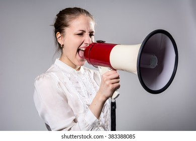Attractive woman with megaphone. Business woman in a white blouse shouting