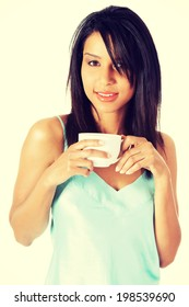Attractive woman in nightwear drinking from cup.