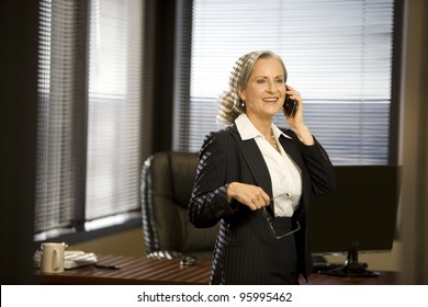 Attractive woman in office talking on cellphone.