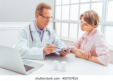 Attractive woman is on consultation at handsome middle aged doctor at  doctors office