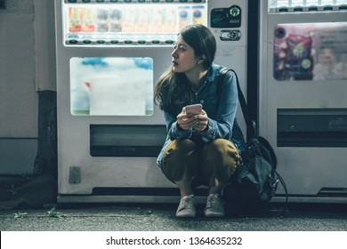 Attractive woman on dark street resting leaning on modern beverage vending machine. young asian lady backpacker using mobile phone waiting for friend in quiet road at night relax kneeling down.