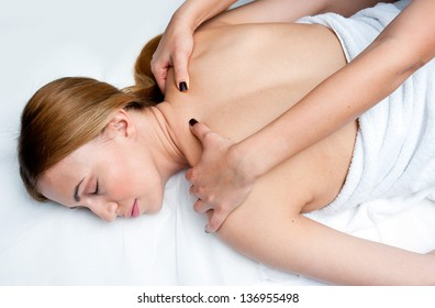 attractive woman on massage table in beauty salon having chiropractic neck adjustment