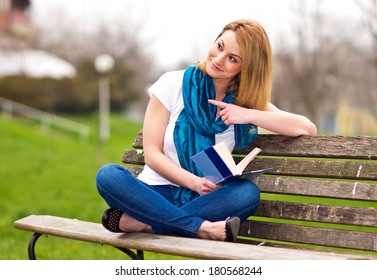 attractive woman on the park bench with book