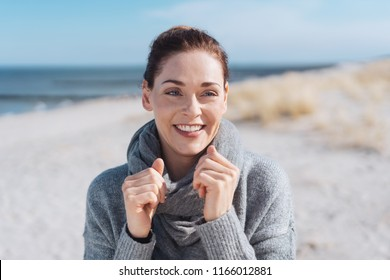 Attractive woman on a sunny beach in cold weather holding her grey scarf with her hands as she looks aside with a lovely friendly smile
