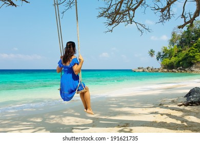 attractive woman on a swing in paradise in a blue dress on a background of the sky, palm trees.