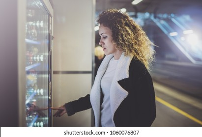 Attractive woman on transit platform using a modern beverage vending machine.Her hand is placed on the dial pad and she is looking on the small display screen