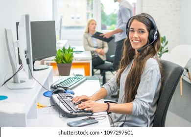 Attractive woman operator agent with headset working on computer in modern office.