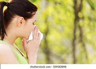Attractive woman outdoor with tissue having allergy.