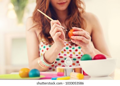 Attractive woman painting Easter eggs at home