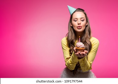 attractive woman with party hat holding cupcake and blowing out candle isolated on pink