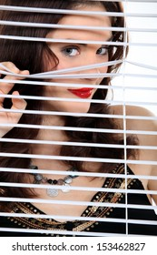 Attractive woman peeking through some blinds