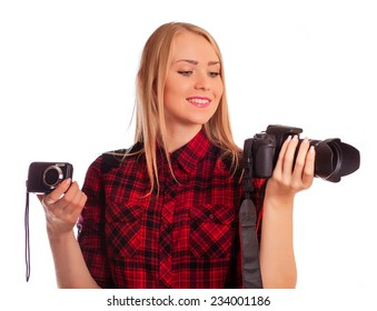 Attractive woman photographer holding two cameras and choosing between professional and compact photo camera - isolated on white