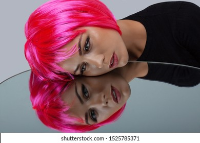 Attractive woman with pink neon hair. Girl looking in the mirror.