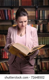 Attractive woman in pink suit reading book in library