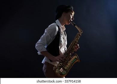 Attractive woman plays saxophone on dark background