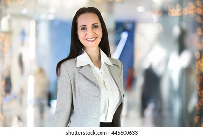 Attractive woman portrait in the office with people blur at the background
