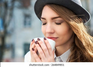 attractive woman poses with white cup. happy smile girl drink smells coffee or tea. city background
