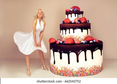 Attractive woman posing like a Marilyn Monroe near big cake. Isolated on pink background.  Congratulation concept