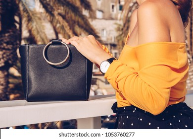 attractive woman posing outdoors on a summer day. fashion blogger in a polka dot skirt, off the shoulder yellow top, wearing sunglasses and holding a metallic handle tote bag. palm trees background