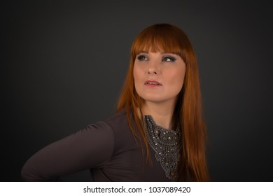 Attractive woman posing in studio: model with red or ginger hair wearing slinky dress